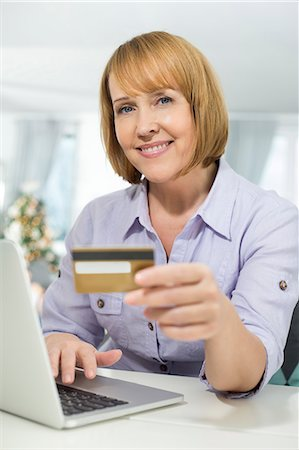ebusiness - Portrait of happy woman shopping online at home during Christmas Stock Photo - Premium Royalty-Free, Code: 693-07673221