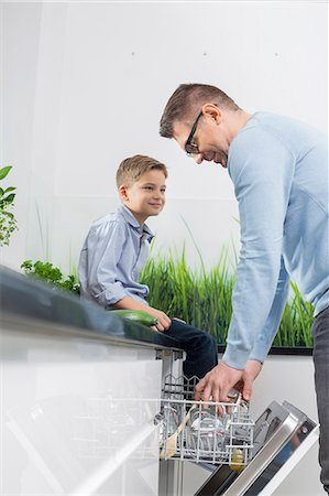 Boy looking at father placing glass in dishwasher at kitchen Stock Photo - Premium Royalty-Free, Code: 693-07673245