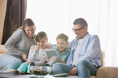 Cheerful family using tablet PC together in living room Stock Photo - Premium Royalty-Free, Code: 693-07673257