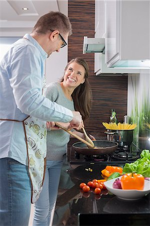 stove - Happy couple preparing food in kitchen Stock Photo - Premium Royalty-Free, Code: 693-07673261