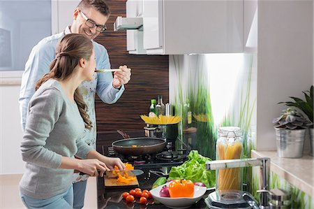 Happy man feeding food to woman cutting vegetables in kitchen Stock Photo - Premium Royalty-Free, Code: 693-07673262