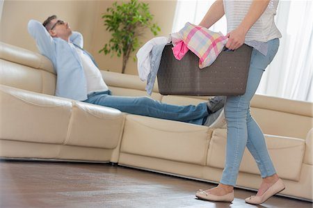 Low section of woman walking with laundry basket while man relaxing on sofa in background Stock Photo - Premium Royalty-Free, Code: 693-07673277