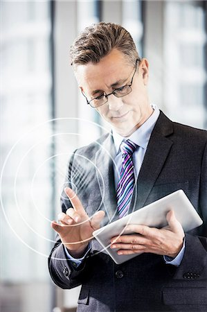 futuristic - Middle aged businessman using digital tablet in office Stock Photo - Premium Royalty-Free, Code: 693-07673302