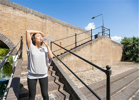 sweaty woman - Tired young woman drinking water on stairs Stock Photo - Premium Royalty-Free, Code: 693-07912080