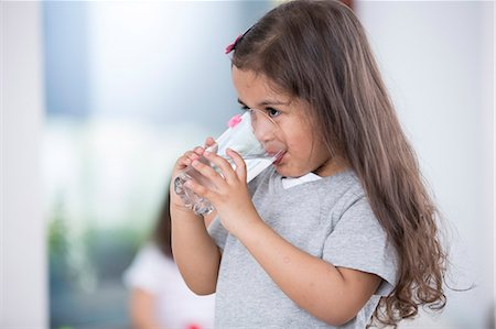 Cute girl drinking glass of water at home Stock Photo - Premium Royalty-Free, Code: 693-07912147