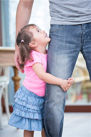 Side view of girl hugging father's leg in house Stock Photo - Premium Royalty-Free, Code: 693-07912142