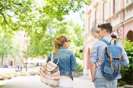 Rear view of young college friends talking while walking in campus Stock Photo - Premium Royalty-Free, Code: 693-07912254