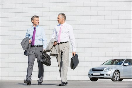 Full length of businessmen with briefcases walking on street Stock Photo - Premium Royalty-Free, Code: 693-07912267