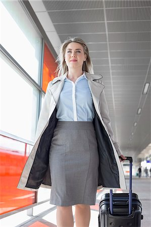 pulling - Young businesswoman with luggage walking in railroad station Stock Photo - Premium Royalty-Free, Code: 693-07912282