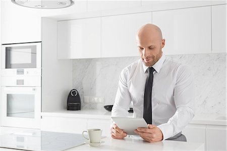 Mid adult businessman using tablet PC in kitchen Stock Photo - Premium Royalty-Free, Code: 693-07912342