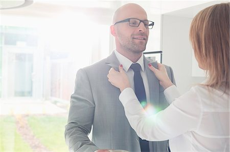 Woman dressing up businessman at home Stock Photo - Premium Royalty-Free, Code: 693-07912357
