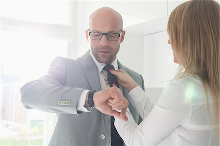 Mid adult businessman checking wristwatch while woman adjusting his tie at home Stock Photo - Premium Royalty-Free, Code: 693-07912358