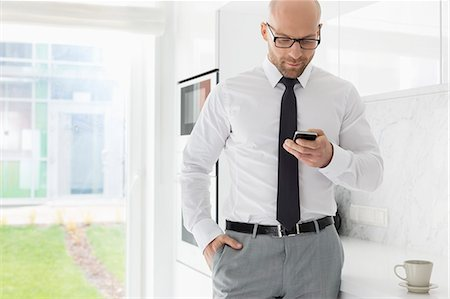 Mid adult businessman text messaging through smart phone at home Stock Photo - Premium Royalty-Free, Code: 693-07912351