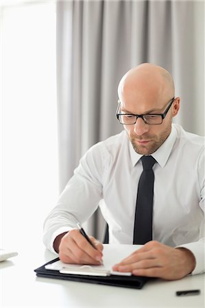 Mid adult businessman writing on clipboard in home office Stock Photo - Premium Royalty-Free, Code: 693-07912364