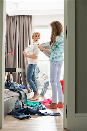 Sisters trying on clothes at home Stock Photo - Premium Royalty-Free, Code: 693-07912387