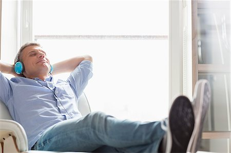 Full-length of relaxed Middle-aged man listening to music at home Stock Photo - Premium Royalty-Free, Code: 693-07912390