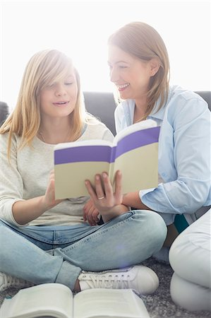 Mother assisting daughter in homework at home Stock Photo - Premium Royalty-Free, Code: 693-07912407