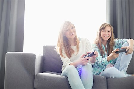 Sisters playing video games on sofa Stock Photo - Premium Royalty-Free, Code: 693-07912408