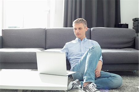 Full-length of man using laptop in living room Stock Photo - Premium Royalty-Free, Code: 693-07912401