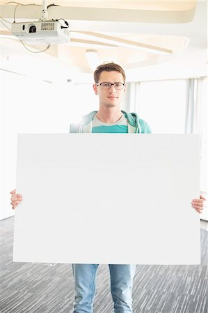 Portrait of confident businessman holding blank board in creative office Stock Photo - Premium Royalty-Free, Code: 693-07912496