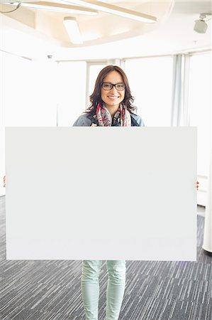 presentation (displaying) - Portrait of happy businesswoman holding blank sign in creative office Stock Photo - Premium Royalty-Free, Code: 693-07912497