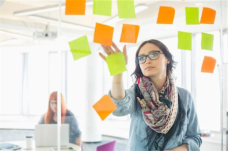 remembered - Creative businesswoman reading sticky notes on glass wall with colleague working in background at office Stock Photo - Premium Royalty-Free, Code: 693-07912498