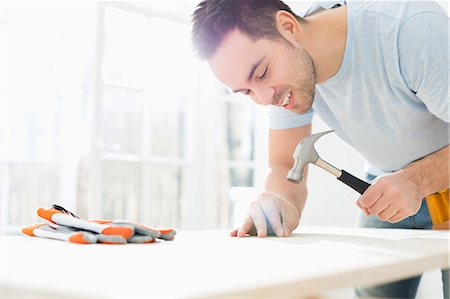 diy or home improvement - Mid-adult man nailing in table Stock Photo - Premium Royalty-Free, Code: 693-07912594