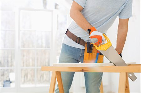diy or home improvement - Midsection of man sawing wood in new house Stock Photo - Premium Royalty-Free, Code: 693-07912595