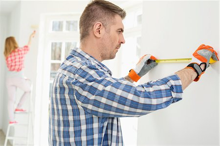 diy or home improvement - Man measuring wall with woman painting in background Stock Photo - Premium Royalty-Free, Code: 693-07912592