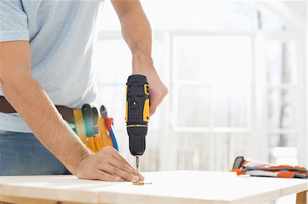diy or home improvement - Midsection of man drilling nail on table Stock Photo - Premium Royalty-Free, Code: 693-07912600