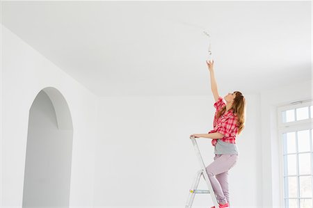 Full-length of woman on ladder fitting light bulb in new house Stock Photo - Premium Royalty-Free, Code: 693-07912619