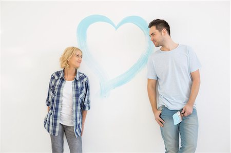 Mid-adult couple looking at each other with painted heart on wall Stock Photo - Premium Royalty-Free, Code: 693-07912647