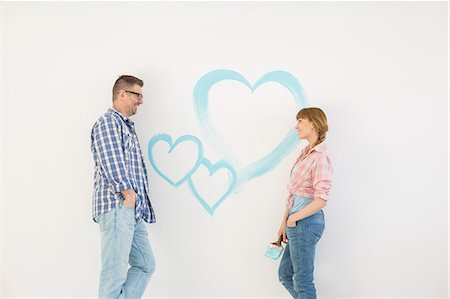 Mid-adult couple looking at each other with painted heart on wall Stock Photo - Premium Royalty-Free, Code: 693-07912649