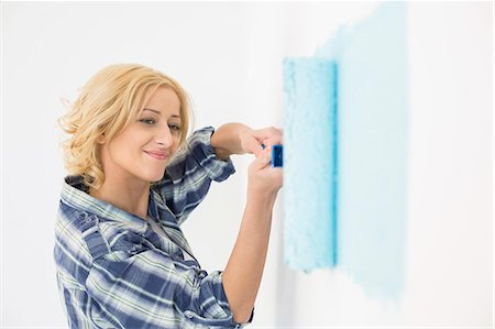 Beautiful woman painting wall with paint roller Stock Photo - Premium Royalty-Free, Code: 693-07912655