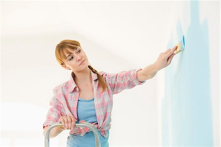 diy or home improvement - Woman on ladder painting wall with paintbrush Stock Photo - Premium Royalty-Free, Code: 693-07912667