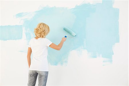 Rear view of woman painting wall with paint roller Stock Photo - Premium Royalty-Free, Code: 693-07912660