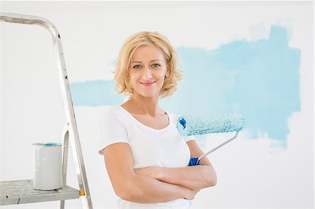 Portrait of woman with paint roller in new house Stock Photo - Premium Royalty-Free, Code: 693-07912661