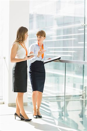 Full-length of businesswomen discussing over tablet PC while standing by railing in office Stock Photo - Premium Royalty-Free, Code: 693-07912685