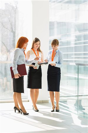 Full-length of businesswomen discussing over documents in office Stock Photo - Premium Royalty-Free, Code: 693-07912686
