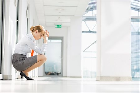 Full-length side view of stressed businesswoman crouching at office hallway Stock Photo - Premium Royalty-Free, Code: 693-07912712