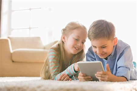 preteen girl - Brother and sister using digital tablet on floor at home Stock Photo - Premium Royalty-Free, Code: 693-07912811