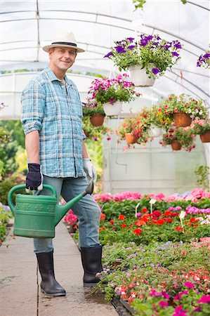 Full-length portrait of smiling man carrying watering can in greenhouse Stock Photo - Premium Royalty-Free, Code: 693-07912858