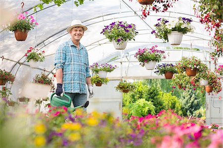 Portrait of happy man carrying watering can in greenhouse Stock Photo - Premium Royalty-Free, Code: 693-07912859