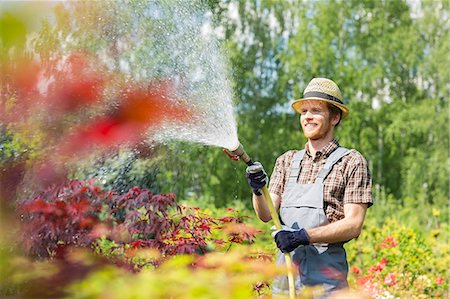 Smiling man watering plants at garden Stock Photo - Premium Royalty-Free, Code: 693-07912914