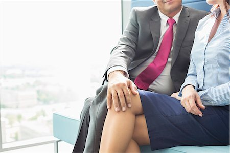flirting - Midsection of businessman flirting with female colleague in office Stock Photo - Premium Royalty-Free, Code: 693-07913295