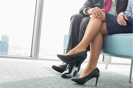 Low section of businessman flirting with female colleague in office Stock Photo - Premium Royalty-Free, Code: 693-07913296