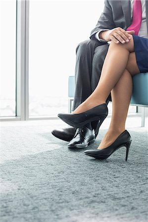 Low section of businessman flirting with female colleague in office Stock Photo - Premium Royalty-Free, Code: 693-07913297
