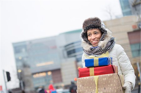 Happy woman looking away while carrying stacked gifts during winter Stock Photo - Premium Royalty-Free, Code: 693-08126888
