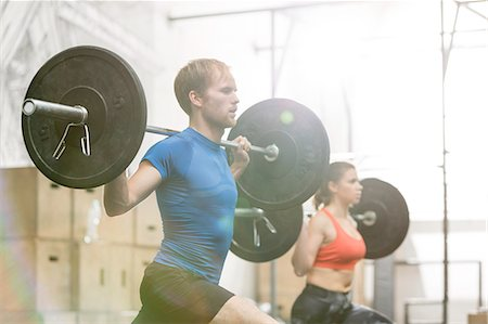 Man and woman lifting barbells in crossfit gym Stock Photo - Premium Royalty-Free, Code: 693-08126922