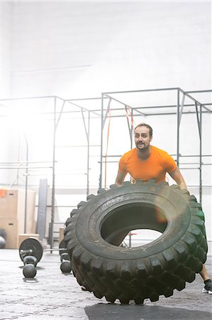 Dedicated man flipping tire in crossfit gym Stock Photo - Premium Royalty-Free, Code: 693-08126938
